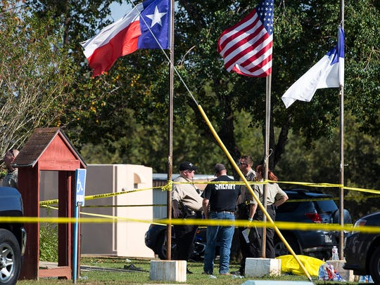 Law enforcement officials stand next to a covered body