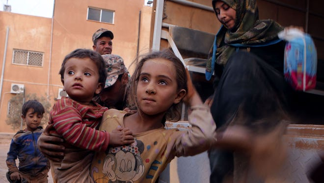 In this AP file photo, Syrian refugees covered in dust arrive at the Trabeel border, after crossing into Jordanian territory with their families, near the northeastern Jordanian border with Syria and Iraq. Syrian refugees covered in dust arrive at the Trabeel border, after crossing into Jordanian territory with their families, near the northeastern Jordanian border with Syria, and Iraq.
