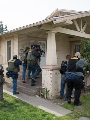 The US Marshals announced the arrests of nearly 400 fugitives in Michigan. Hundreds more were arrested nationwide as part of a six-week operation. This photo is of a March raid in  Fresno, California.