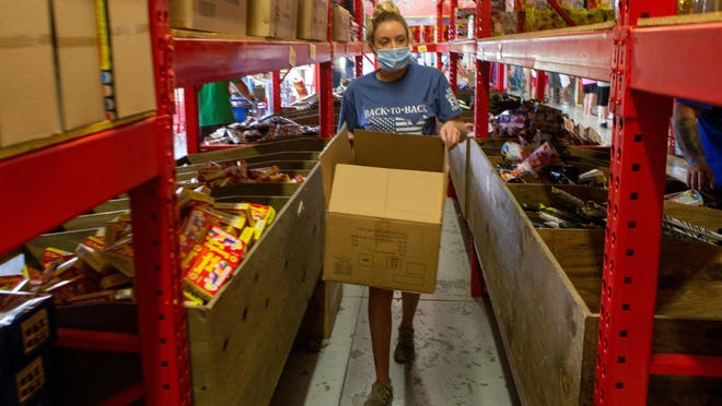 """Meranda Carter, an employee at Jake's Fireworks, 2045 S.E. 45th St., restocks popular firework items Friday afternoon. """"We are out of almost everything,"""" Carter said. """"Its going to be chaos the next couple of days."""""""