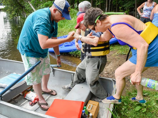 World War II veteran Norbert Jost, 92, gets help into the boat from fellow veterans Nick Neurohr, Fairmont, Hans Paschke, Blue Earth, and his daughter Mary Sebas, Fairmont, Saturday, June 30, on Lake Sagatagan in Collegeville.