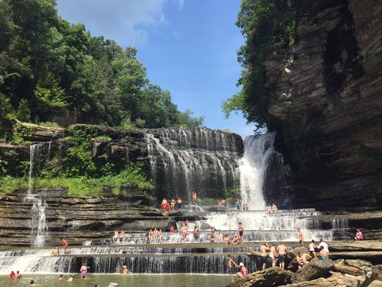 People cool off in the waterfall at Cummins Falls State