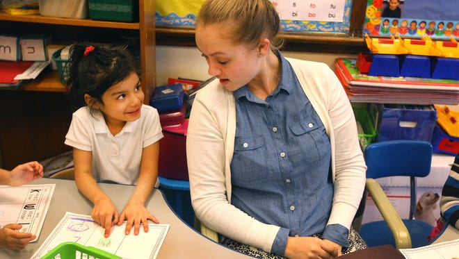 Kidielys Diaz, from Puerto Rico, a kindergarten student at School 12, works with teacher Rachel Reff as part of a bilingual program for grades K-6 in the Rochester School District. Parents are asking the district to expand the program through eighth grade.