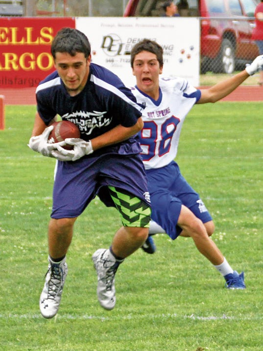 Bill Armendariz — Headlight Photo   George Ortiz pulls in a Dante Urrea pass in front of a Hot Spring High defender during last Tuesday's 7-on-7 passing drills at Deming High's Memorial Stadium. Teams from Cobre and Silver also competed in the drills designed to help skilled position players get in sync during the off-season. The Deming Wildcats will take their off-season passing game to Truth or Consequences, NM on Tuesday for a 7 p.m. competition.