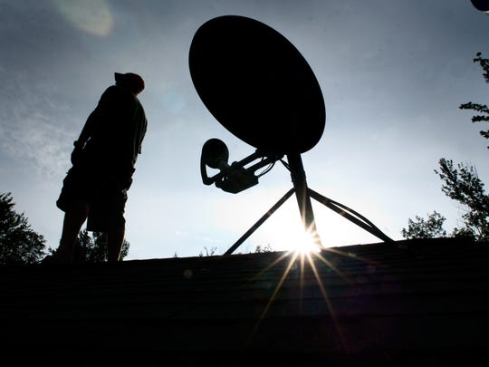 Whether in search of broadband internet or television, many residents rely on satellite signals. Here, Jeff Synder of Underhill, Vermont, watches the skies from the roof of his home in 2010.