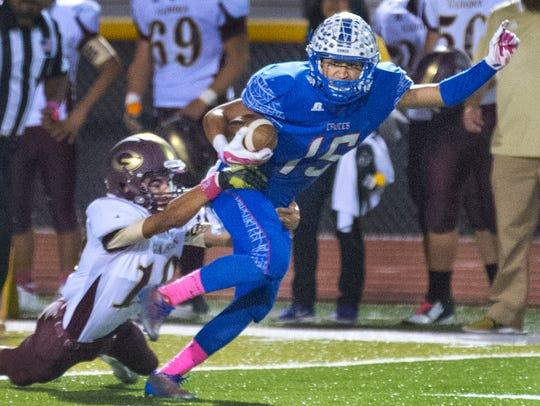 Las Cruces receiver Brandon Baeza works to break a