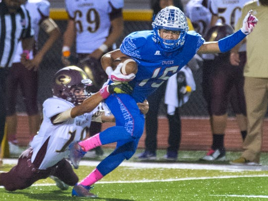 Las Cruces receiver Brandon Baeza works to break a tackle on Thursday night at the Field of Dreams.