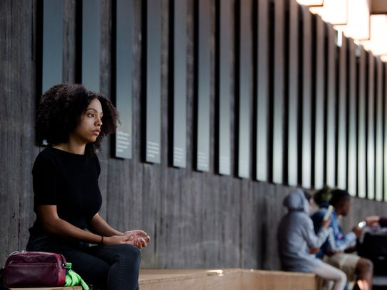 A visitor sits quietly at EJI's National Memorial for