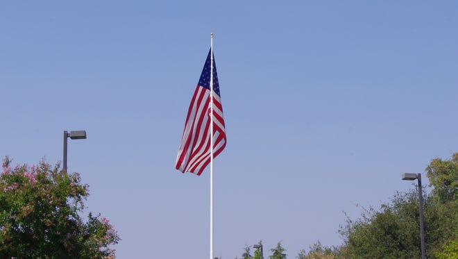 The large American flag near Interstate 5 in central Redding remained at full staff for much of Monday, until President Donald Trump ordered government officials to lower the flag to half-staff at federal facilities.