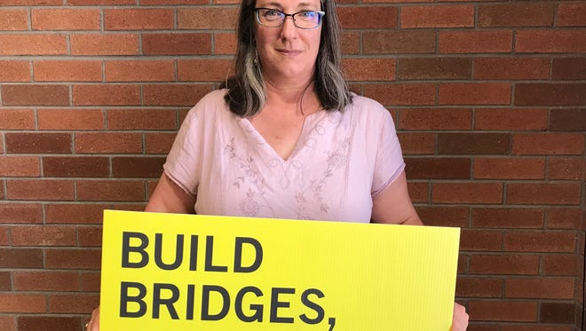 Lynnda Schilling, the organizer for the Tempe chapter of Amnesty International, poses with a poster.