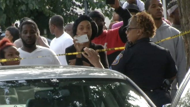 A crowd of people, some using cell phone cameras to record the events, watches as police respond at a shooting scene.