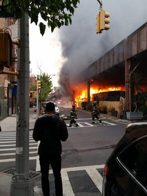 In this photo provided by Ben Parkin, firefighters battle a fire under the Metro-North railroad tracks in New York, Tuesday. Train service into and out of Grand Central is being delayed due to the fire.