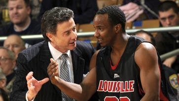 In this file photo, Louisville coach Rick Pitino, left, talks with guard Andre McGee. The NCAA accused Louisville of four violations stemming from its investigation into allegations that a former basketball staffer hired escorts and strippers for sex parties with recruits and players.