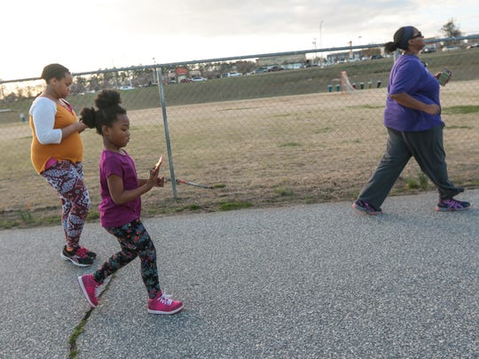 Zy'Keeyah Rice, left, Ty'leah Holloway, middle, and Manetti Rice, all of Anderson, walk on Thursday afternoon at the McCants walking track in Anderson.