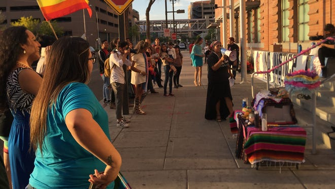 """Attendees gather around the """"open mic"""" held on April 6, 2018, by Trans Queer Pueblo, Center for Neighborhood Leadership, Black Lives Matter Metro Phoenix, Raíz of Planned Parenthood, Arizona Black Voters Initiative, and Arizona Coalition to End Domestic and Sexual Violence."""