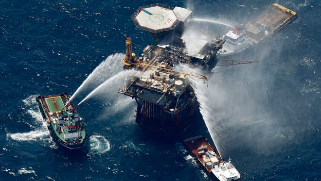 In this file photo taken Sept. 2, 2010, boats are seen spraying water on an oil and gas platform that exploded in the Gulf of Mexico, off the coast of Louisiana. All 13 crew members were rescued. The moratorium on exploration in the eastern Gulf established in 2006 will expire in 2022 unless Congress acts.