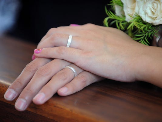 A couples shows their wedding ring durin