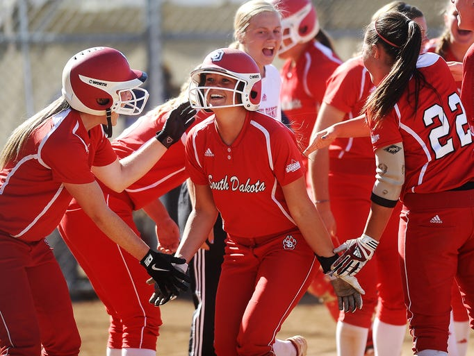 USD's Katie Dinning (15), center, reacts with teammates after hitting a two run homerun during the second game of a doubleheader against SDSU on Friday, April 25, 2014, in Brookings, S.D. (Joe Ahlquist / Argus Leader)
