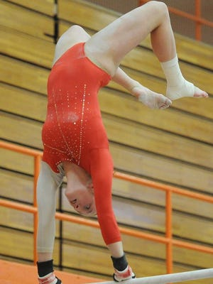 New Palestine's Annabelle Dockins competes on the uneven bars. IHSAA Regional Gymnastics Championships were held at Columbus East High School Friday March 14, 2014.
