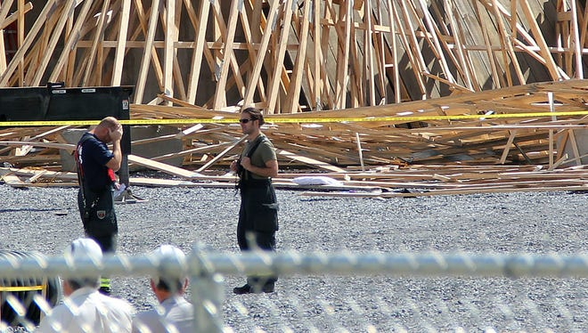 Construction workers and first-responders speak to each other after a building collapsed on Avenue A in Williston on Aug. 7, 2014. The building was under construction to be a salt shed for Williston. Several people trapped under debris suffered minor injuries.
