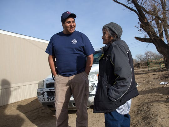 Eric Trevizo, vice president of the Shiprock Authorized Local Emergency Response Team, talks with Ina Yazzie at her home in Shiprock on Wednesday.