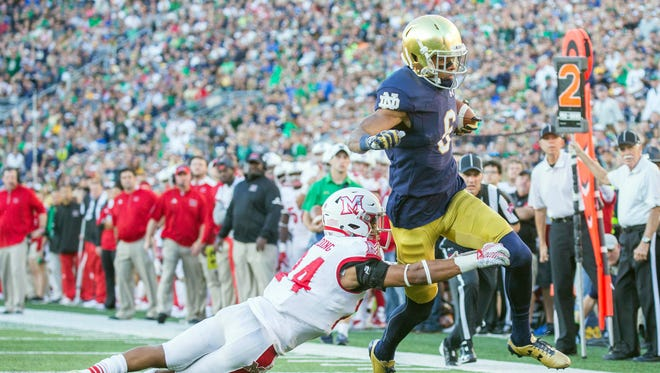 Notre Dame Fighting Irish wide receiver Equanimeous St. Brown (6) catches a pass and runs with the ball as Miami (Oh) Redhawks defensive back Heath Harding (24) defends in the first half of the game at Notre Dame Stadium.