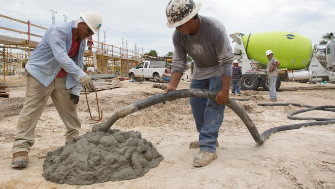 Juan Duboa, left, inserts a rebar handle into the last  bit of unused concrete for easy lifting  at a Creighton Construction site in Fort Myers.