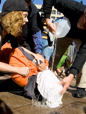 Protestors demonstrate the use of water boarding to volunteer Maboud Ebrahim Zadeh, Monday, Nov. 5, 2007, in front of the Justice Department in Washington. The demonstration was to highlight the use of water boarding as torture, to protest the nomination of Attorney General-designate Michael Mukasey.