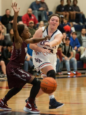 Reagan Lantier of LCA makes a pass by White Castle's Jabreion Brown  in their Class 1A state regional game on Monday night in Lafayette.