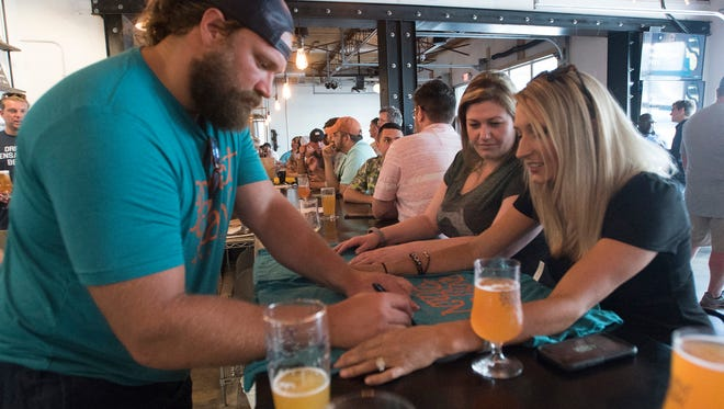 Pensacola native and Miami Dolphins football player, Josh Sitton, signs autographs for Ashley Rogers, right, and Sarah Wade while he mans the bar at the Perfect Plain Brewery in downtown Pensacola Friday, June 22, 2018.