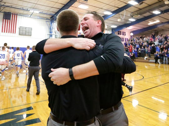 WLA boys basketball head coach Jeremiah Hoffmann celebrates with another coach after Mitch McFarlane makes the game winning shot as time expires in overtime against the Omro Foxes. The win gives WLA a share of the conference title.
