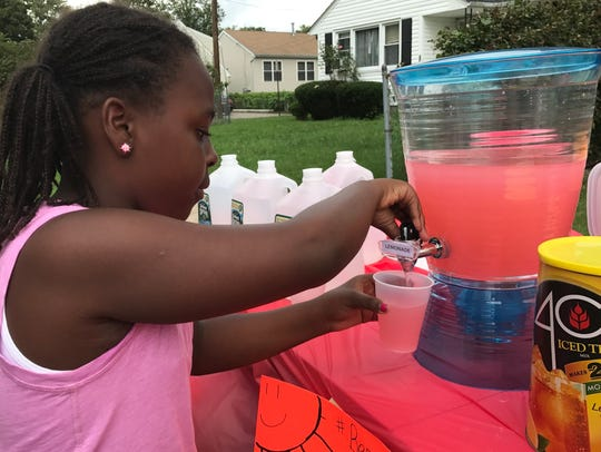 Laila Little, 10, pours a cup of pink lemonade during