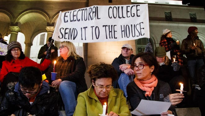 Protesters opposed to U.S. President-elect Donald Trump petition to the Electoral College on the eve of its vote during a candlelight vigil in Los Angeles.