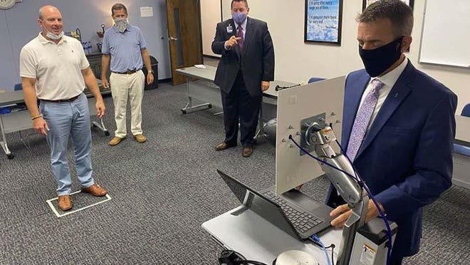 """Carteret County Board of Education Chairmen John """"Bubba"""" McLean and Clark Jenkins are shown a Thermal Imaging Unit by the school system's Chief Technology Officer Mike McKay and Superintendent Rob Jackson. These units will be used by schools in the fall for the students temperatures to be taken."""