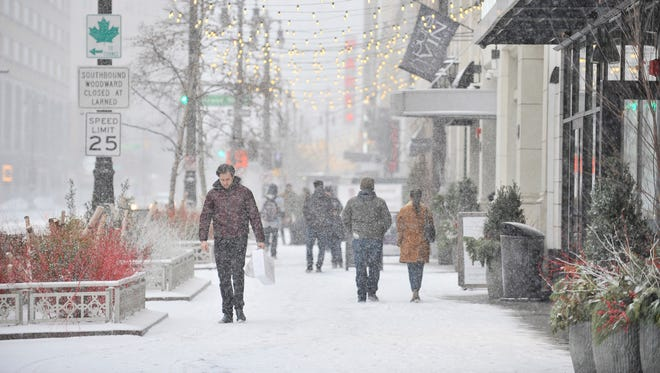 Steven Jamail of New York City, left, walks up Woodward Avenue while snow falls in Detroit on Dec. 24, 2017. Jamail got some last minute gifts for his partner who in Elf the Musical at the Fox Theatre.