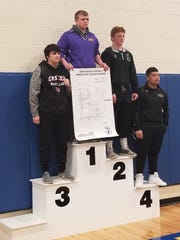 Bronson's Chase Gibson stands atop the podium after winning the 215-pound weight class at the Division 4 Individual Districts.