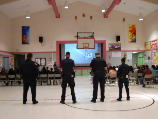 Salinas police officers stand in the back of the room