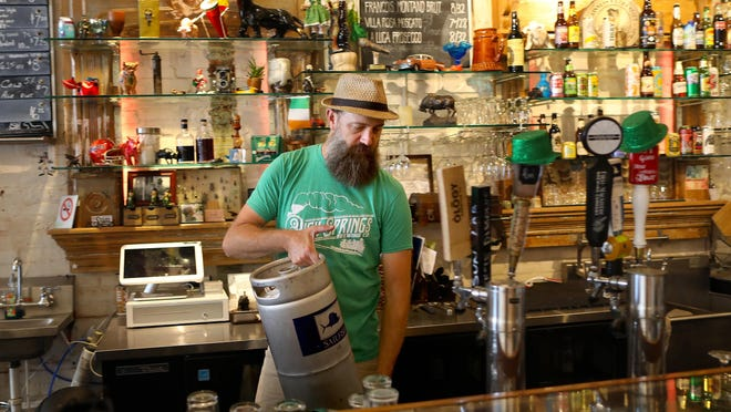 Jacob Larson, owner of The Bull in downtown Gainesville, picks up a keg of beer that went bad after a cooler in the bar broke sometime since it closed for the pandemic. Larson, who feels that its not yet time to open his bar, came in Thursday to clean up the cooler.