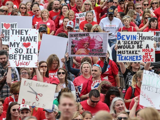 Thousands of teachers held signs during Friday's protest