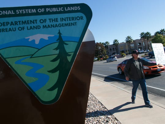 Ernie Jessop, a resident of Motoqua who is concerned about the Bureau of Land Management's land use plans for the area around his home, holds a sign to protest the plan outside the St. George offices of the BLM Thursday, Nov. 12, 2015.