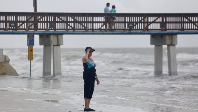 Sandy Narr, who is visiting from Pittsburgh, looks out over the Gulf of Mexico as a rain system moves through Fort Myers Beach recently.