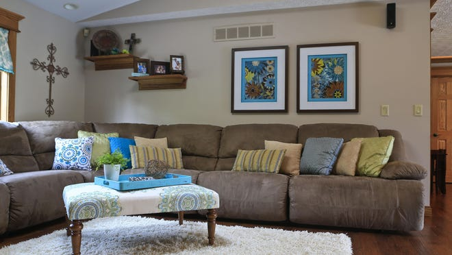The family room on the main level features a curved sectional with bright pillows. Prints adorn the wall.