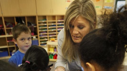 Teacher Jenny Davis works with first-graders using tablets at Mason Early Childhood Center last year. The new Common Core standards require students to be taught and tested on computers and tablets