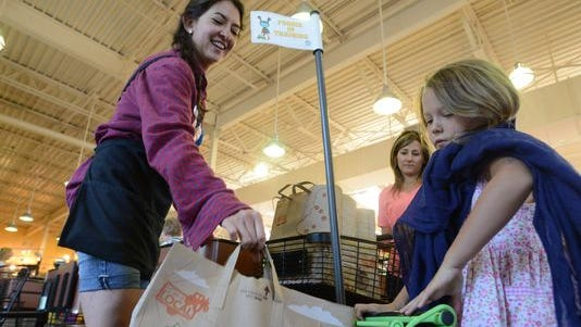 Cashier Ona Fisher, left, puts a bag of groceries into Elliana Beno's kids cart Tuesday at Whole Foods market . Whole Foods stopped offering plastic bags in 2008 and offers a 10-cent credit for each reusable bag customers bring in.