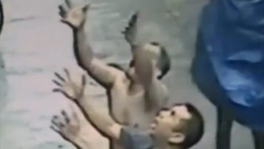 A photo taken from video shows men reacting as a baby falls from a balcony.