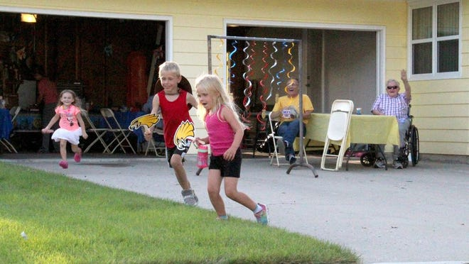 At Michelle Beeghly's house, kids scramble to get candy tossed in the grass by a passing Crookston Classic Cruiser.
