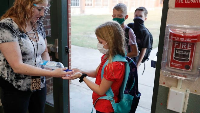 In this Aug. 5, 2020, file photo, wearing masks to prevent the spread of COVID19, elementary school students use hand sanitizer before entering school for classes in Godley, Texas. As schools reopen around the country, their ability to quickly identify and contain coronavirus outbreaks before they get out of hand is about to be put to the test.