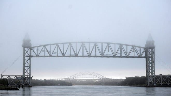 A heavy fog lingers over the Railroad Bridge and Bourne Bridge about an hour before sun set Wednesday.