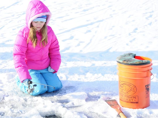 Vanessa Dresser waits for a bite while ice fishing at the Lexington Harbor. The Free Winter Fishing Weekend is Feb. 16-17.