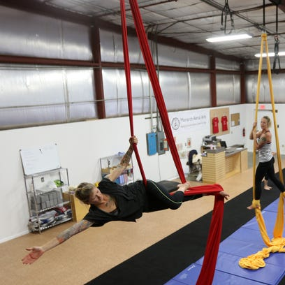 Students stretch while balancing mid-air at practice